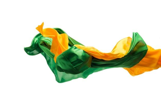 Гладкая элегантная прозрачная желтая, зеленая ткань разделена на белом фоне.