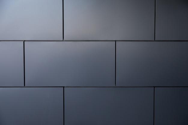 Smooth grey metal tiled wall half in shadow