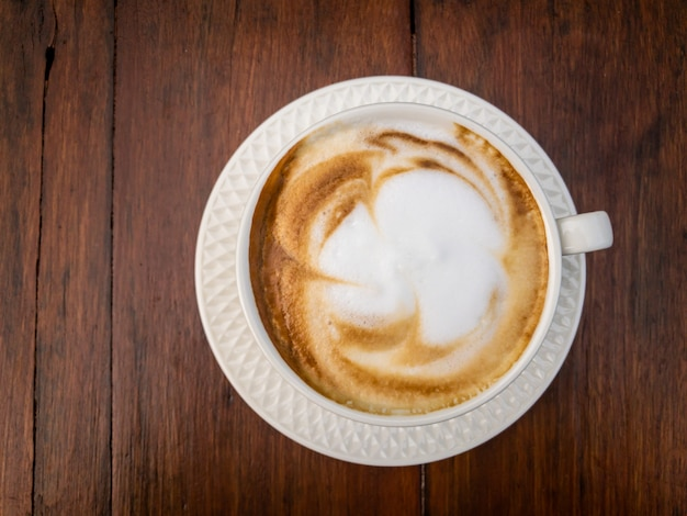 Smooth hot milk foam of cappuccino coffee on the beautiful vintage wooden table close up.