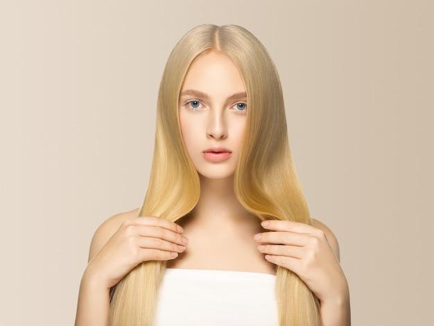 滑らかな長いブロンドの髪の女性は、健康な肌を自然に構成します。ベージュに。