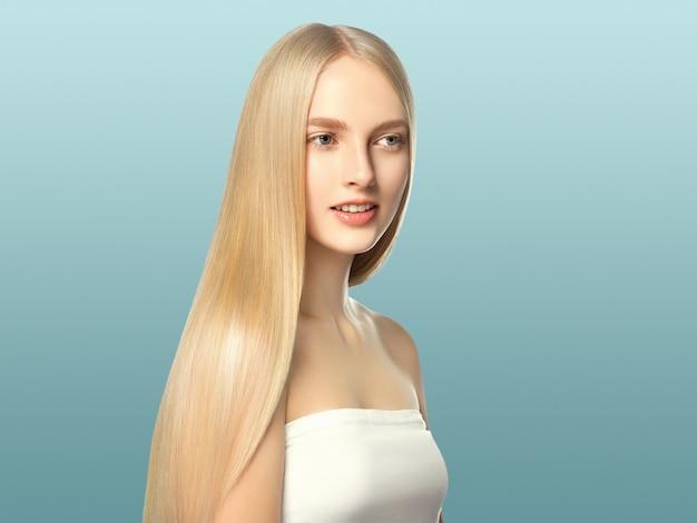 滑らかな長いブロンドの髪の女性は、健康な肌を自然に構成します。青に。
