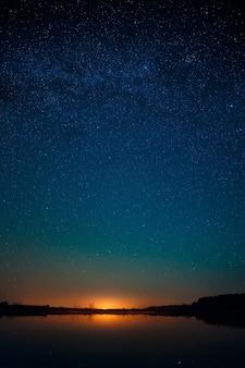 Ровная поверхность озера на фоне звездного неба