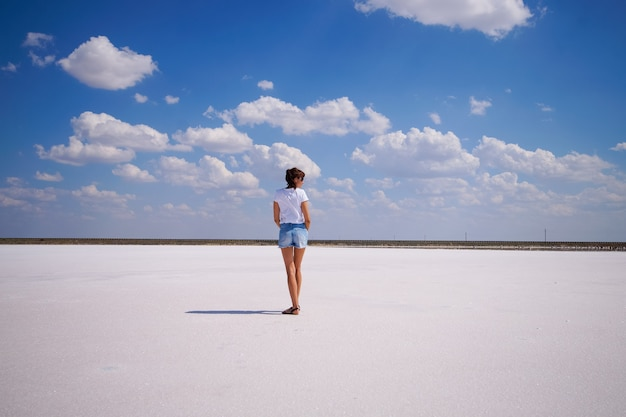The smooth surface of the salt crust and the blue sky with clouds is empty space recreation