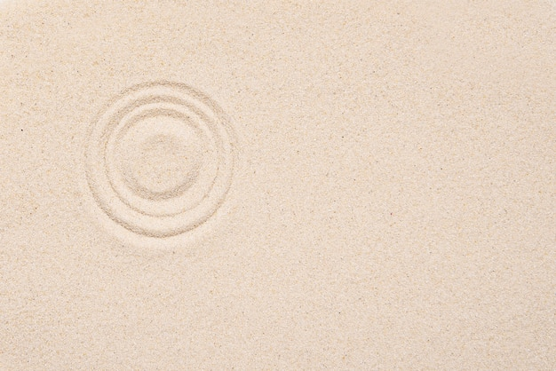 Smooth texture of white sand with round pattern on sandy background.