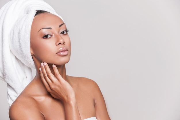 スムーズなタッチ。彼女の頬に触れてカメラを見ている美しい若いアフリカ系アメリカ人の上半身裸の女性