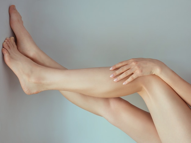 Гладкие женские ножки после лазерной эпиляции, положив руку на колено.