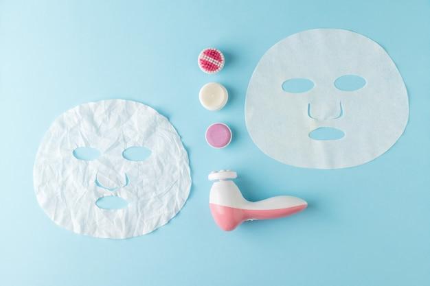 Разглаженные и мятые маски для лица и массажер на синем фоне. концепция омолаживающего воздействия на кожу.