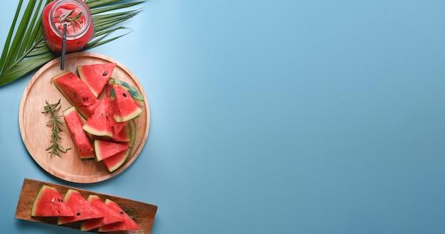 Смузи и нарезанный свежий арбуз на синем фоне.