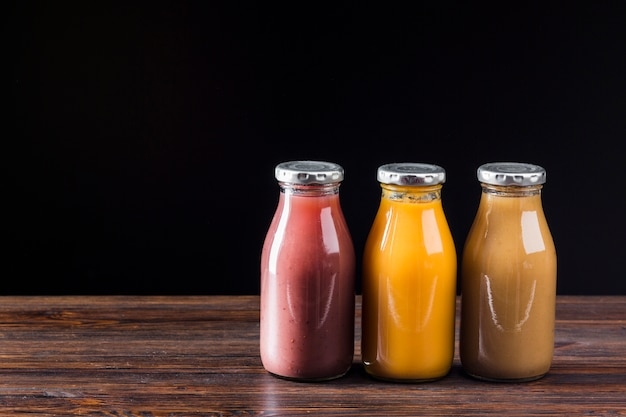 Smoothie bottles on wooden surface