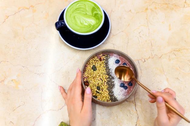 スムージーボウルローフード、抹茶ラテグリーンティーカップ、金属スプーンで女性の手、準備ができて、テーブルの上