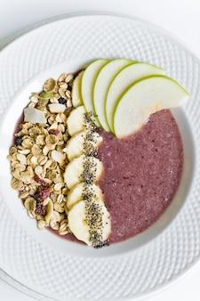 Smoothie bowl with banana, apple, chia seeds, granola and yogurt.