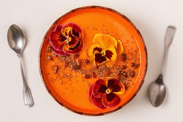 Smoothie bowl with edible pansy flowers, chia seeds, goji berries