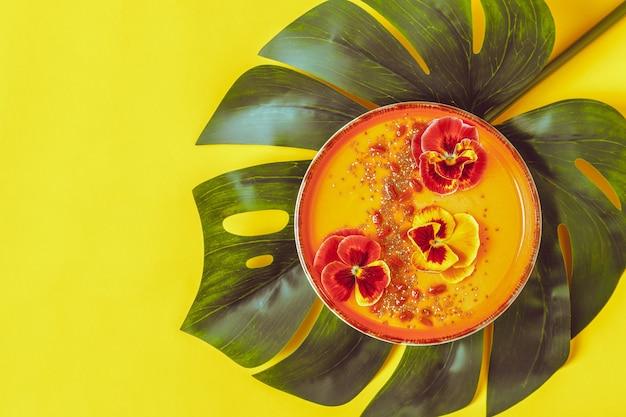 Чаша для смузи со съедобными цветами анютиных глазок, семенами чиа и ягодами годжи