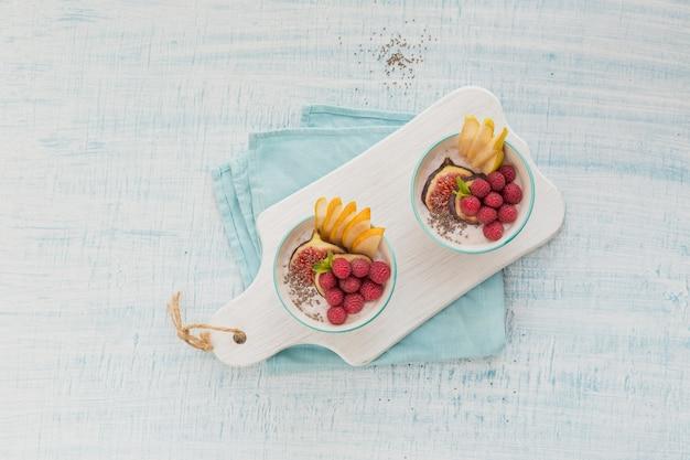 건강한 채식 채식 아침 식사를 위해 신선한 과일, 치아 씨앗, 라즈베리, 무화과 흰색 소박한 나무 표면에 스무디 그릇. 건강 식품 개념. 위