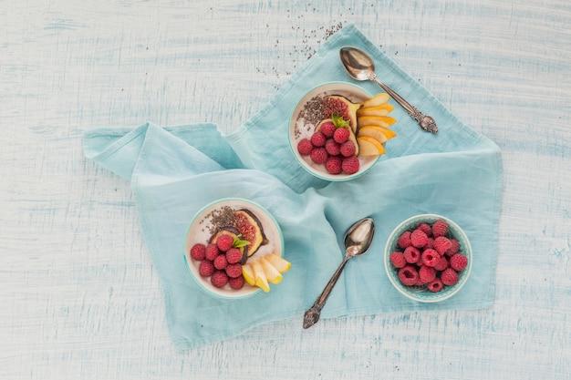 건강한 채식 채식 아침 식사를 위해 신선한 과일, 치아 씨앗, 라즈베리, 무화과 흰색 소박한 나무 표면에 스무디 그릇. 건강 식품 개념. 플랫 레이