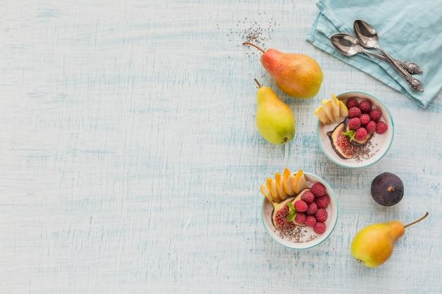 건강한 채식 채식 아침 식사를 위해 신선한 과일, 치아 씨앗, 라즈베리, 무화과 흰색 소박한 나무 표면에 스무디 그릇. 건강 식품 개념. 평면도