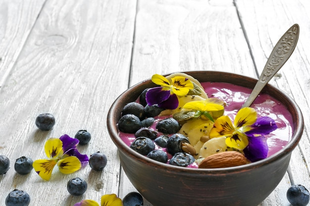 Smoothie bowl with a spoon topped with fresh berries, banana, chia seeds, nuts and flowers for healthy breakfast