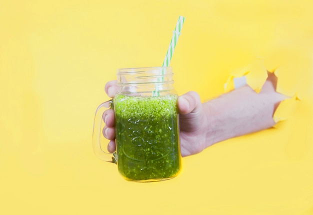 Smoothie from fresh herbs in a glass jar is held by a man's hand in a hole