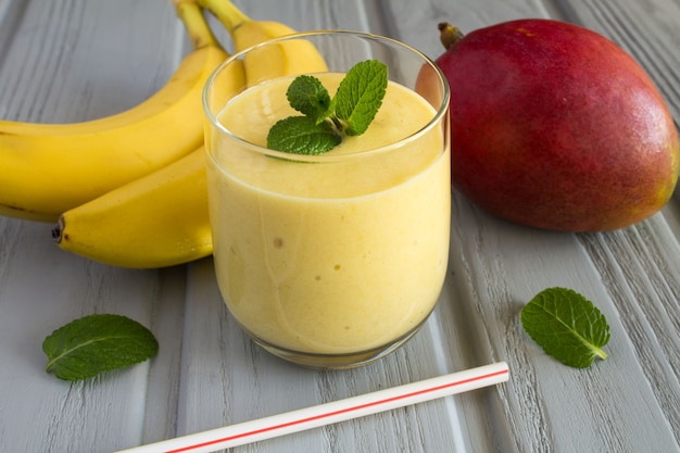 Smoothie from mango and banana on the grey wooden