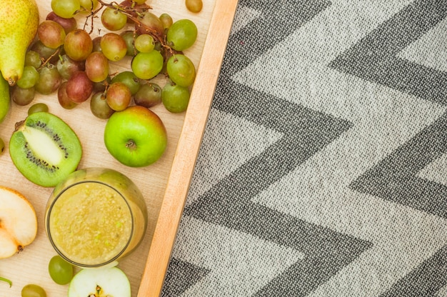 Smoothie and fruits in wooden crate on tablecloth