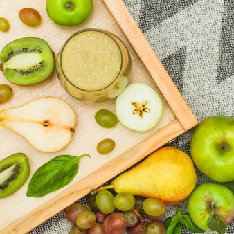 Smoothie glass and fresh fruits on wooden tray and over tablecloth