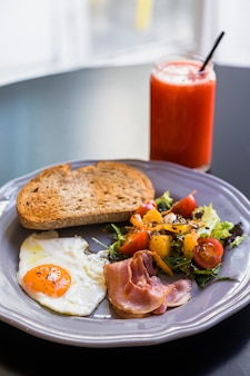 Smoothie in glass jar; toast; bacon; fried egg; salad on gray plate over the black table
