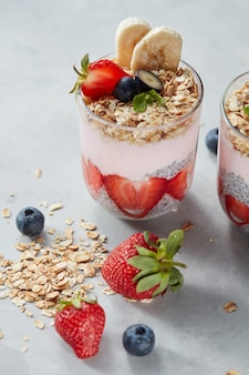Smoothie in glasses with fruits strawberry, banana, blueberry, oat flakes and chia