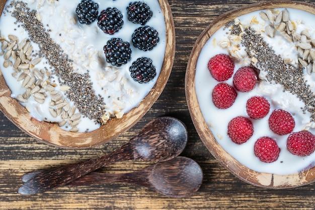 아침 식사로 블랙베리, 라즈베리, 오트밀, 해바라기 씨, 치아 씨를 곁들인 코코넛 그릇에 스무디가 있습니다. 건강한 식생활, 슈퍼푸드의 개념. 평면도