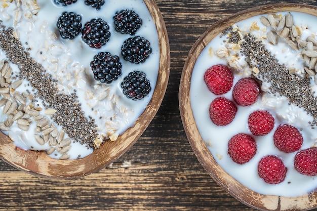 朝食にブラックベリー、ラズベリー、オートミール、ヒマワリの種、チアシードを入れたココナッツボウルのスムージーをクローズアップします。健康的な食事、スーパーフードの概念。上面図