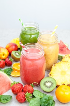 Smoothie jars surrounded by sliced fruits and berries