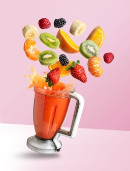 Smoothie mixer with drink and fruit flying ingredients, isolated on pink background