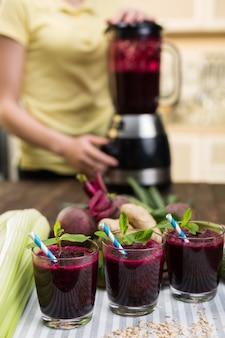 キッチンテーブルの上のビートと新鮮な野菜のスムージー