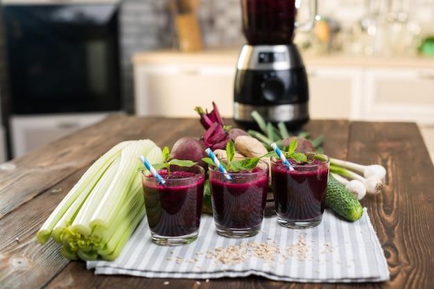 キッチンテーブルのビートと新鮮な野菜のスムージー