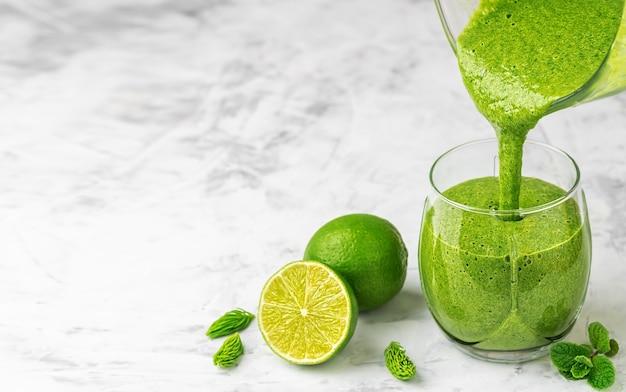 신선한 과일, 녹색 시금치, 슈퍼 푸드 스무디를 잔에 붓습니다.