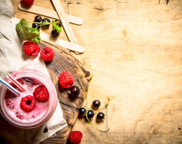 Smoothie raspberry and blackcurrant. on wooden background.