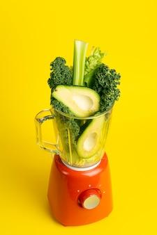 スムージーのレシピ。黄色の背景にミキサーで野菜(アボカド、セロリ、カレサラダ、ほうれん草)の緑のスムージー。ビーガンと健康食品のデトックスコンセプト