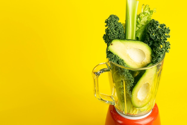 Smoothie recipe. green smoothie of vegetables (avocado, celery, cale salad, spinach) in a blender on a yellow background. vegan and healthy food detox concept