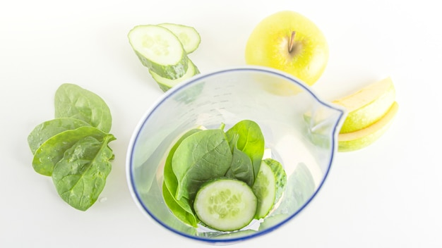 Smoothie recipe. ingredients for green smoothie: spinach, apple, cucumber in blender. home cooking. vegan healthy detox eating, dietary and weight loss drink.