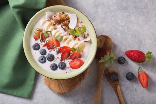 Smoothie or smoothy bowl with granola, fruits and seeds.  organic probiotic drink or yogurt  with strawberry, on the white grey background. gut health. fermented dairy beverage. trendy food.