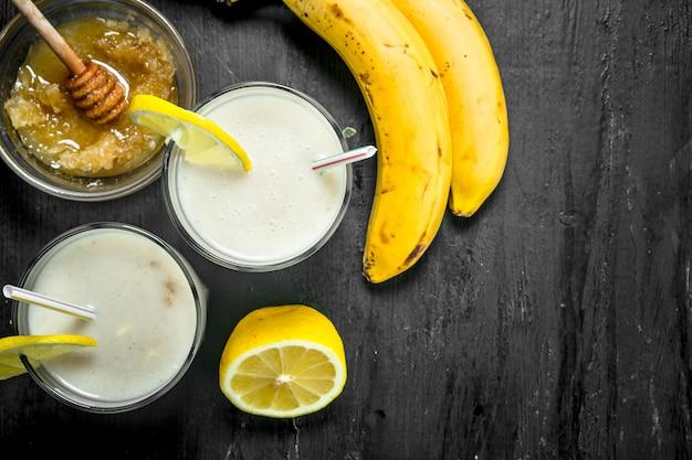 バナナ、レモン、ミルクのスムージー。素朴な背景に。