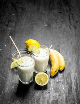 バナナ、レモン、牛乳のスムージー。素朴な背景に。