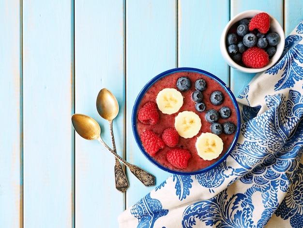 Смузи с бананом, малиной и черникой на синем деревянном столе