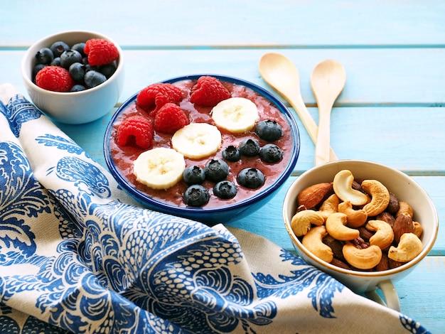 Смузи с бананом, малиной, черникой и орехами на синем деревянном столе