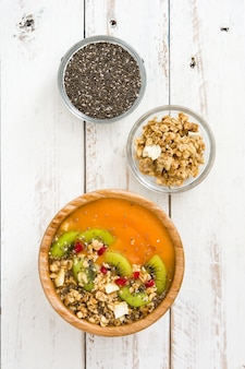 Smoothie with fruit cereals and chia on white wooden table