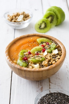 Smoothie with fruit,cereals and chia on white wooden table
