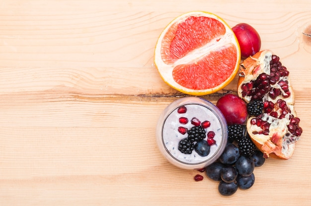 Smoothie with halved grapefruits; plum; grapes; blackberries and pomegranate on wooden backdrop