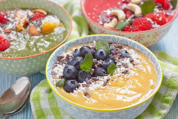 Smoothie with mango, greens and raspberry decorated with berries and nuts