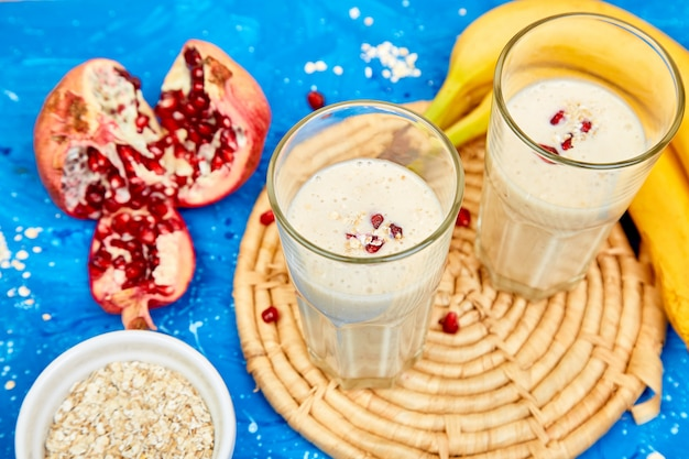 Smoothie with oat or oatmeal, banana and pomegranate on blue.