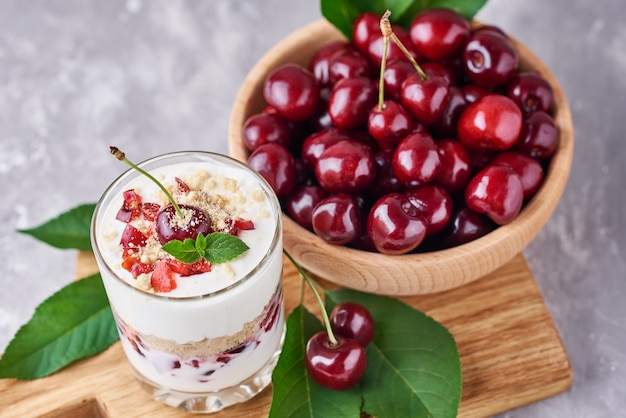 Smoothie with summer cherry in glass jar and fresh berries  in wooden bowl