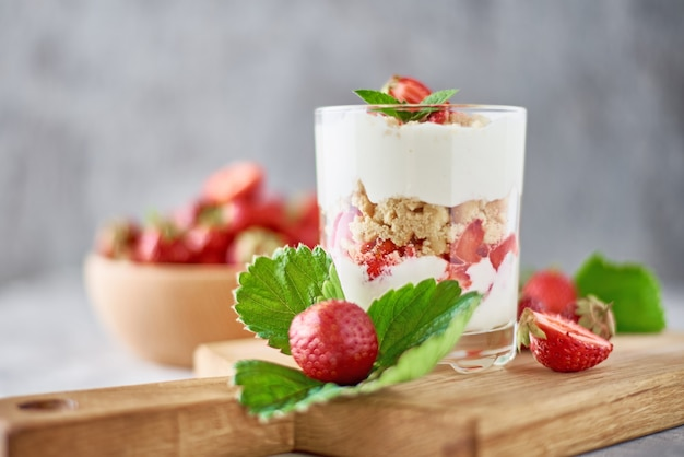 Smoothie with summer strawberry in glass jar and fresh berries  in wooden bowl on a gray